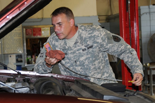 CW2 Brian Crowe, Warrant Officer Career College, checks the oil on his vehicle at the automotive skills center. The center offers free labor on oil changes throughout November if people bring in their own oil and filters.