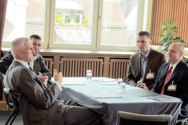 From left to right, Lt. Gen. Mark Hertling, commanding general, U.S. Army Europe, talks with Command Sgt. Maj. Bentura Fernandez, 409th CSB, Col. William Bailey, 409th commander, and Kim Denver, DASA (P), about the synchronization of Army contracting agencies within Europe.