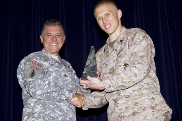 Marine Sgt. Zachary Coates receives an award from Defense Language Institute Foreign Language Center Commandant Col. Danial D. Pick. Coates is the 2011 Department of Defense Language Professional of the Year.