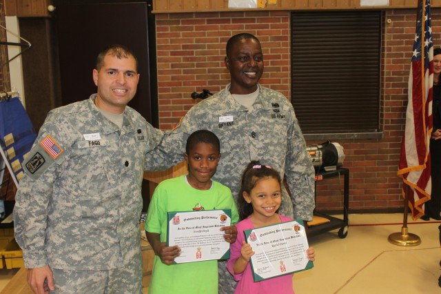 Lt. Col. Robert Fago, 44th ESB commander, and Command Sgt. Maj. Charlie Bryant present awards to Grafenwoehr Elementary School students Norelle Doyle and Rachel Owens at the school's STAR Assembly, Oct. 25.