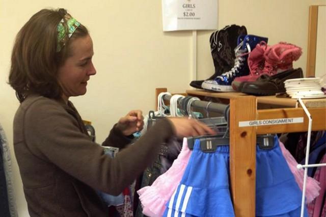 Cindy Burt, a Kaiserslautern Landstuhl Spouses Association employee gets shelves and items ready for the opening of the new Pulaski Barracks thrift store at U.S. Army Garrison Kaiserslautern.