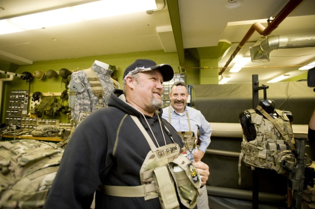 """Larry the Cable Guy"" models a chest rig designed for him by Rich Landry, in background, during a Nov. 8, 2012, visit to the Load Carriage Design Lab while filming a segment at Natick Soldier Systems Center for his ""Only in America"" series. Rather than holding items Soldiers often carry in combats such as ammunition, batteries, or multi-tools, Larry's modular chest rig was designed to hold his beer, cigars, lighter and TV remote control. The segment will air Wednesday, July 17, at 9 p.m. on the History Channel."