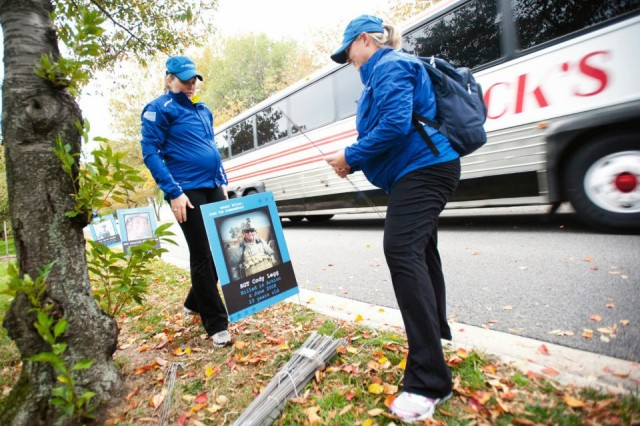 Shella Hightower, left, and Erin O'Connor post signs honoring fallen service members along the wear blue mile portion of the annual Marine Corps Marathon in Washington D.C.