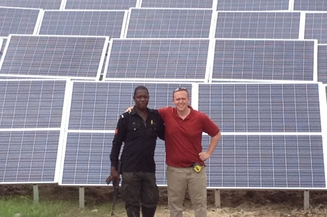 A SunDial solar generator system is being set up in Tebu, Nigeria. Keegan Cotton, vice president, SunDial, stands with a Nigerian police officer.  In addition to being used by Special Forces Soldiers in Afghanistan, these systems have been deployed for oil companies, railroads, mining companies and a number of non-governmental organizations.