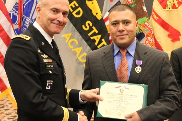 After being wounded in combat, Spc. Miguel Ramos, is recognized for his bravery as he is presented the Purple Heart and certificate by Lt. Gen. David H. Huntoon Jr., United States Military Academy Superintendent, during a Warrior Care Month banquet hosted by the Soldier and Family Assistance Center at the West Point Club, Nov. 8, 2012.