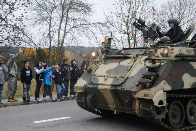 Hohenfels Community Members wave as one of the vehicles used by Hohenfels' world class Opposition Force rolls down the street during the Veterans Day parade, Nov. 8.