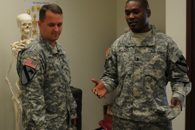 "FORT HOOD, Texas "" 1st Lt. Jermain Williams (right), battalion medical officer for 3-82 FA Regt. ""Red Dragons,"" 2nd BCT, 1st Cav. Div., takes 1st Cav. Div. surgeon Lt. Col. William Porter on a tour of an exam room in the Red Dragons' aid station here, Nov. 6"