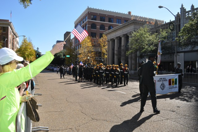 Jacksonians wave to JROTC cadets as they march through the streets of downtown Jackson during the city's first-ever Veterans' Day parade.