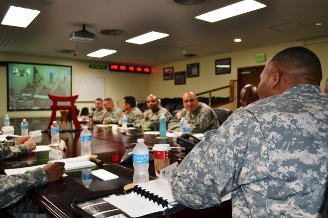 Command Sgt. Maj. Steven L. Payton, command sgt. maj., USARJ, looks at the big screen as he listens to a brief via teleconference from the 35th Combat Sustainment Support Battalion, located on mainland Japan.