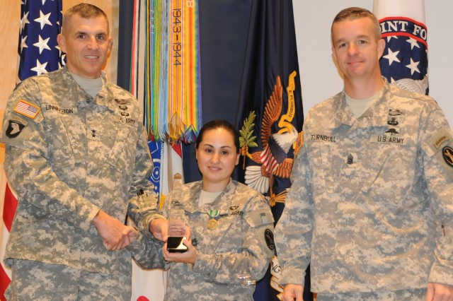 The newly selected Joint Force Headquarters-National Capital Region and the U.S. Army Military District of Washington 2013 Career Counselor of the Year, Sgt. 1st Class Christina Dauria-Cox receives the Army Commendation Medal  and the JFHQ-NCR/MDW 2013 Retention Award by Maj. Gen. Michael S. Linnington, JFHQ-NCR/MDW commanding general, and Command Sgt. Maj. David O. Turnbull.