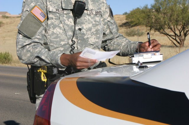 Spc. Daniel Willis, 18th MP Detachment, writes a citation for speeding after stopping a car for traveling 14 miles over the posted speed limit.