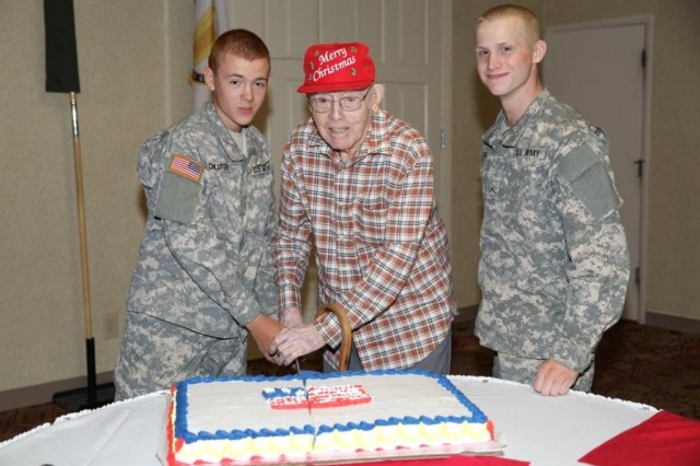 From left, Pvt. Ryan Schluter, 18, Jim Burnett, 94, and Pvt. Jacoby Kellog, 18, cut the cake during the Military Affairs Committee Veterans Day luncheon held at the Thunder Mountain Activity Centre on Nov. 7.