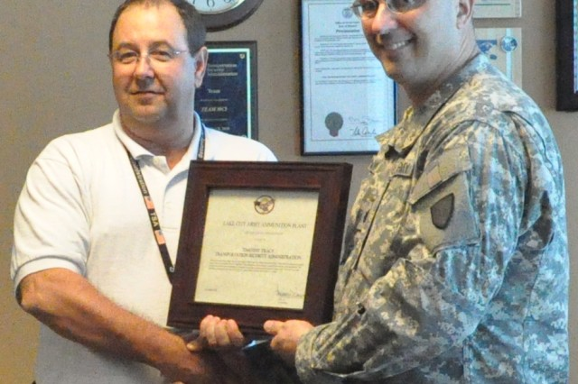 Lt. Col. Lawrence Cannon, commander of Lake City Army Ammunition Plant, presents an appreciation award to Timothy Tracy, an explosives specialist/bomb scene officer with TSA at Kansas City International Airport.