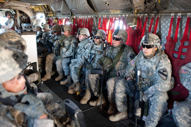 An observer controller/trainer, top left, from 1st Battalion, 351st Aviation Regiment, 166th Aviation Brigade, Division West, ensures that Soldiers of Company B, 1st Battalion, 8th Cavalry, 2nd Brigade Combat Team, 1st Cavalry Division, are secure aboard a Chinook helicopter prior to taking off on an air movement operation at Fort Hood, Texas, in September. The 166th Aviation Brigade recently trained the Chinook unit, the California Army National Guard's Company B, 1st Battalion, 126th Aviation Regiment, for a deployment to Afghanistan.