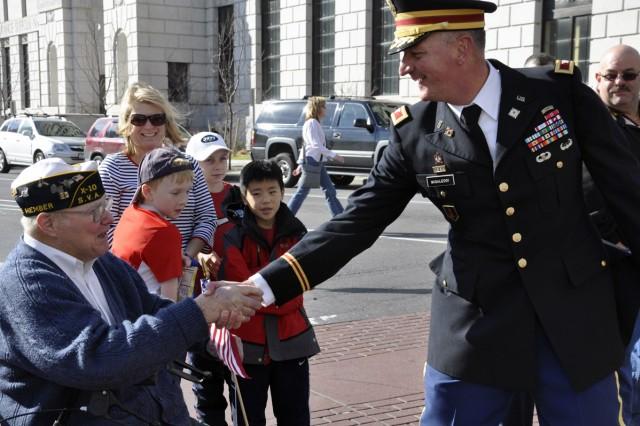 Col. Mark F. Migaleddi breaks ranks to thank a Veteran along the parade route.