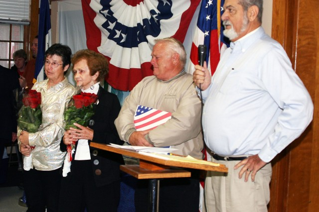 (From left) Patricia Bickford, Phyllis Sondergard, Norman Bickford and West Branch Mayor Donald Kessler stand in front of a packed room in the West Branch Municipal Building as the crowd applauds their efforts to spearhead the creation of Appreciation Park and the completion of the Veteran's Monument inside the park. West Branch held its Veterans Day ceremony and monument unveiling Nov. 11. Sgt. Maj. Duane Strong, Distribution Management Center, Army Sustainment Command, was the keynote speaker for the event. (Photo by Barbara Toner, ASC Public Affairs)