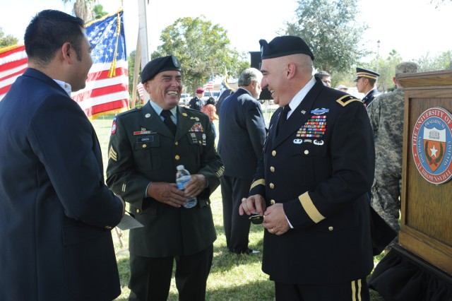 "BROWNSVILLE, Texas "" Brig. Gen. Orlando Salinas (right), U.S. Army South deputy commanding general, visits with Sgt. (Retired) Carlos Garza and other guests after the University of Texas at Brownsville Veterans Day ceremony here Nov. 8."