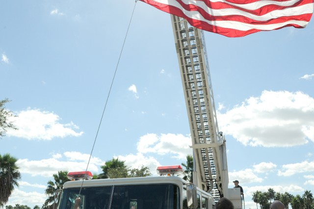 "BROWNSVILLE, Texas "" Brownsville Fire and Rescue members raise the American flag prior to the start of the University of Texas at Brownsville Veterans Day ceremony here Nov. 8."