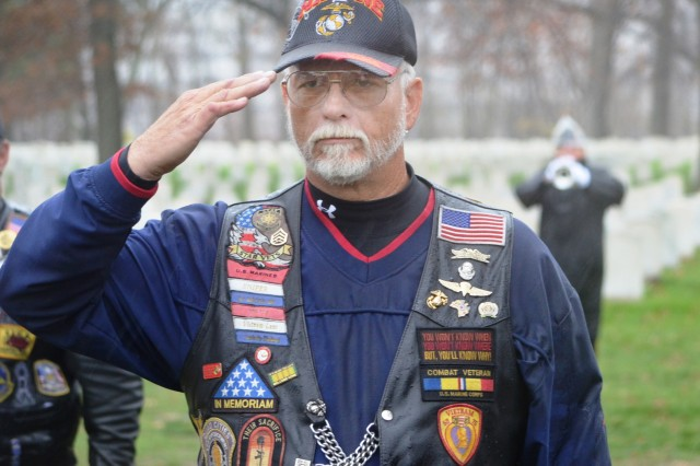 A Vietnam veteran salutes during the playing of Taps at the Rock Island National Cemetery Veterans Day ceremony, Nov. 11. About 100 people braved the rain, wind and cold to pay respect to our nation's veterans.  (Photo by Dan Carlson, ASC Public Affairs)