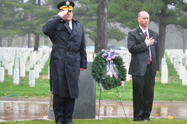 Brig. Gen. John F. Wharton, commanding general, Army Sustainment Command, and Douglas Ledbetter, director of the Rock Island National Cemetery, pay respect to fallen veterans by placing a wreath at the foot of the cemetery's flagpole and monument. Gold Star families, veterans, elected officials and members of the community braved the rain, wind and cold to pay respect to our nation's veterans. (Photo by Dan Carlson, ASC Public Affairs)