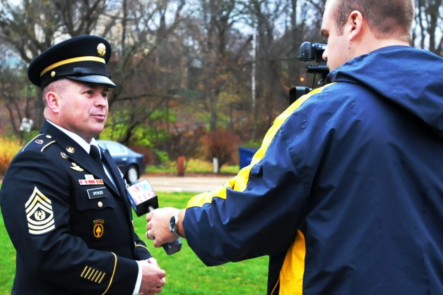 Command Sgt. Maj. James E. Spencer, command sergeant major, Army Sustainment Command, is interviewed by reporter Taylor Umland, KWQC-TV 6, following the Veterans Day ceremony at the Veterans Memorial Park Nov. 11. (Photo by Jon Connor, ASC Public Affairs)
