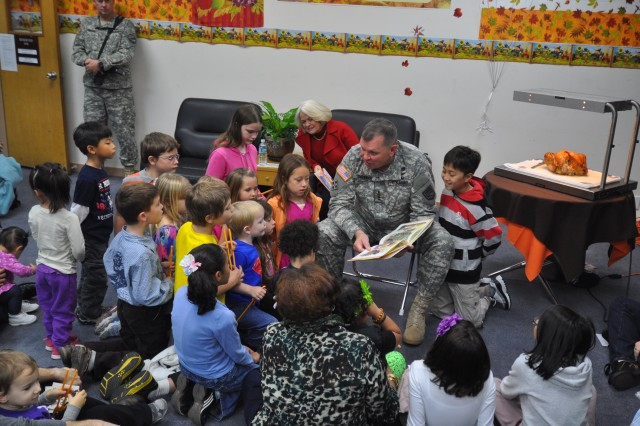 Gen. James D. Thurman, commander of United Nations Command, Combined Forces Command, and U.S. Forces Korea, reads a book amid a crowd of high-spirited children during the annual Thanksgiving Story Time held in the Yongsan Library, Nov. 10. (U.S Army photo by Pvt. Lim Hong Seo)