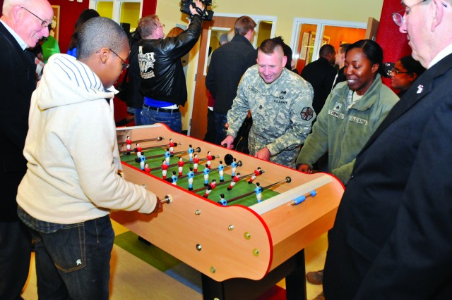 James W. Corriveau, left, Fort Drum Public Works director, and Command Sgt. Maj. Mark H. Oldroyd, garrison command sergeant major, play foosball Friday with a teen and a Soldier after the Youth Center's grand opening while Michael H. McKinnon, deputy to the garrison commander, looks on.