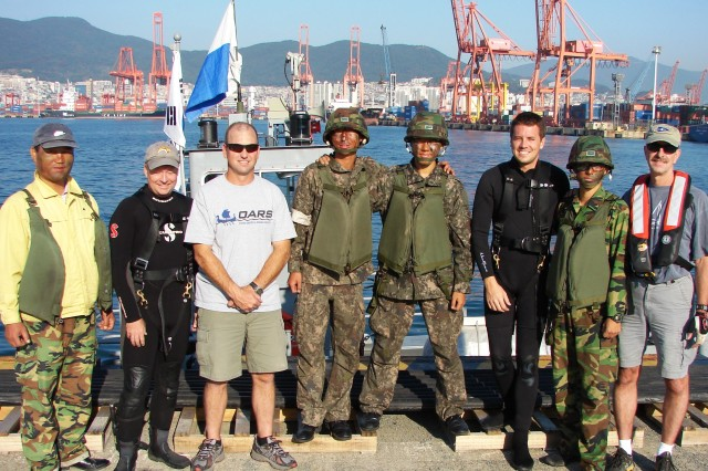 Flanked by members of the Republic of Korea Army who served as boat crew for the U.S. Army Corps of Engineers Forward Response Dive Team during their October underwater inspection of Pier 8 in Busan, South Korea, are (from left to right) Shanon Chader of Buffalo District; Team Lead Todd Manny of Portland, Ore.; Kyle Tanner of Nashville; and Ed Gawarecki of Buffalo, N.Y.