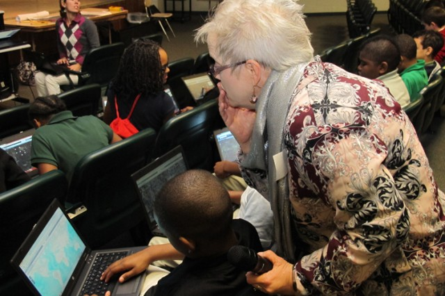 Beverly Richey, geographer and GIS specialist at Huntsville Center, helps a sixth-grader at Ed White Middle School use an online map Nov. 14 during a Geographic Information System activity at the school. More than 150 sixth-graders  participated in the GIS Day workshop led by the Corps of Engineers Huntsville Center employees. The school was among six schools in Alabama that observed GIS Day.