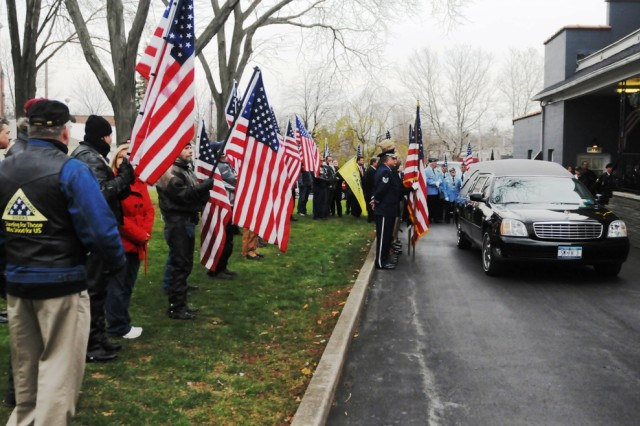Patriot Guard Riders, military officials, and residents of Seneca Falls, N.Y., wave flags as the hearse carrying Cpl. Elmer Kidd's casket drives by. Kidd served with the 32nd Infantry Regiment in Korea, and his remains were recently returned home.