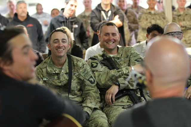 """PAKTYA PROVINCE, Afghanistan - Staff Sgt. Serge McAvoy (left) and Sgt. Jeremy Macdonald, both assigned with 1st Battalion, 187th Infantry Regiment, 3rd Brigade Combat Team """"Rakkasans,"""" 101st Airborne Division (Air Assault), laugh during a song played by members of the Nashville to You Tour, at forward operating base Gardez, Nov. 15, 2012. The tour featured Nashville's top songwriters and performers as they traveled throughout Afghanistan performing for deployed Soldiers. (U.S. Army Photo by Sgt. 1st Class Abram Pinnington, TF 3/101 PAO)"""