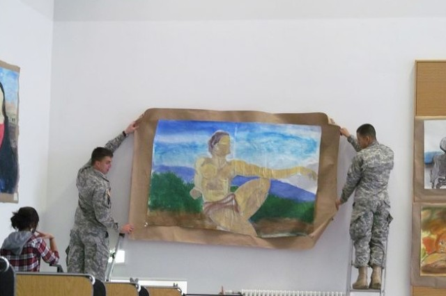 "First Lt. Tillman Busbee (left) and Spc. Angel Trevino, both from the 527th Military Police Company, help hang the ""500 Years Later "" 1512-2012"" display at the Hohenfels Middle High School."