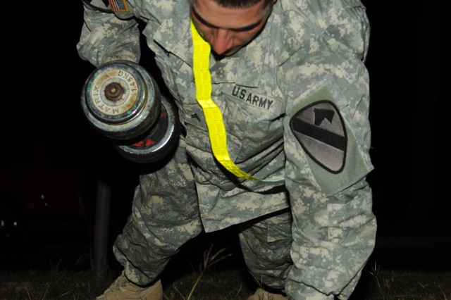 """FORT HOOD, Texas -- Cpl. Casey Hill, a cavalry scout with Troop B., 4-9 Cav. """"Dark Horse,"""" 2nd BCT, 1st Cav. Div., performs a modified pushup utilizing dumbbells during the 3.2-mile, round robin Dark Horse Noncommissioned Officer Physical Fitness Challenge here, Nov. 2."""