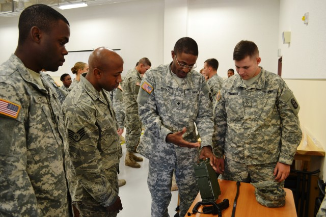 Spc. Kevin Arnold, patriot switch operator, Charlie Battery, 1st Battalion, 1st Air Defense Artillery (Regiment), teaches how to set frequencies on the Single Channel Ground and Airborne Radio System (SINCGARS) during the 10th Regional Support Group Joint Communications Training at Torii's Training Support Center.  Soldiers from the 10th RSG and Airmen from 18th Communications Squadron, Kadena Air Base, gathered to learn how to effectively work together as a joint communications team.