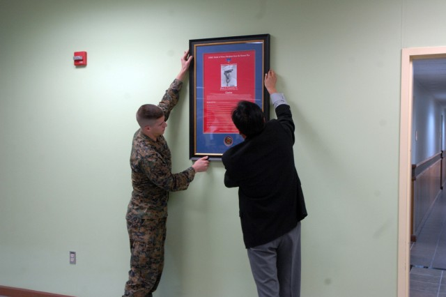 A poster for remembrance of Lt. Commiskey who bravely fought at the Korea War is being hung on the wall of Commiskey's Community Activity Center during ribbon cutting ceremony for opening Commiskey's Community Activity Center, Nov. 19. (U.S. Army photo by Cpl. Lee Hyokang)