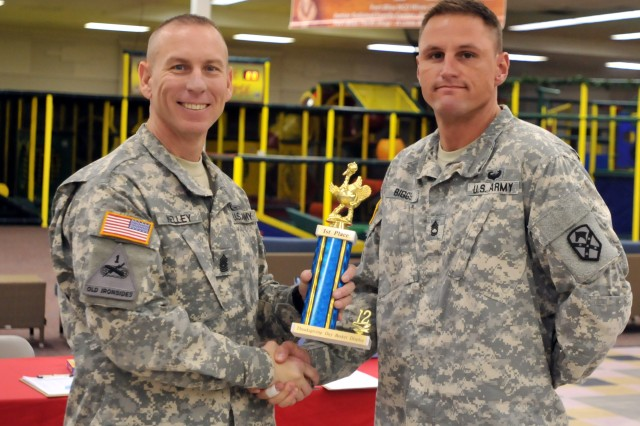 Command Sgt. Maj. Ronnie R. Kelley, command sergeant major, 1st Armored Division and Fort Bliss, presents the first place trophy to Sgt. 1st Class Matthew Biggs, the 15th Sustainment Brigade Mortuary Affairs noncommissioned officer, at the conclusion of the annual Team Bliss Thanksgiving food basket drive at the Fort Bliss Trading Post Nov. 19.