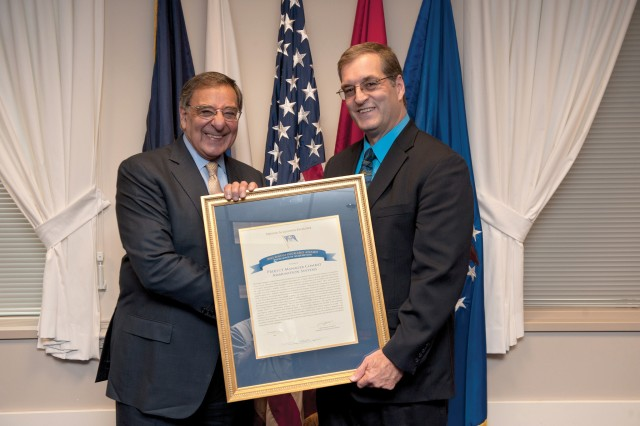 Secretary of Defense Leon E. Panetta presents a 2012 David Packard Excellence in Acquisition Award to Rene Kiebler, Deputy Project Manager Combat Ammunition Systems.