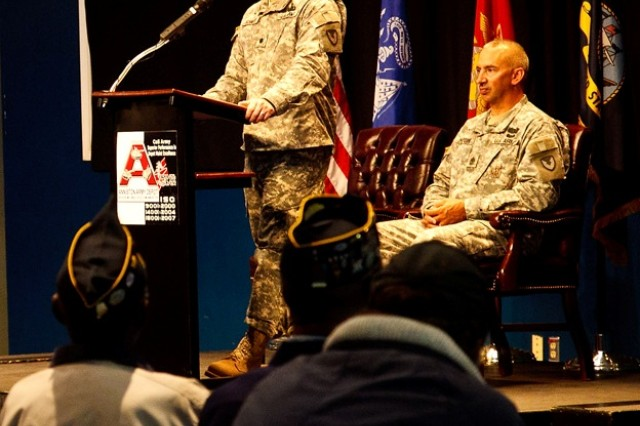 Lt. Col. David Schmitt, commander of Anniston Munitions Center, speaks during the ceremony, reminding the crowd present that members of the military serve their country and their families for life. Seated on the stage is Sgt. Maj. Jeffrey Marcon of ANAD.