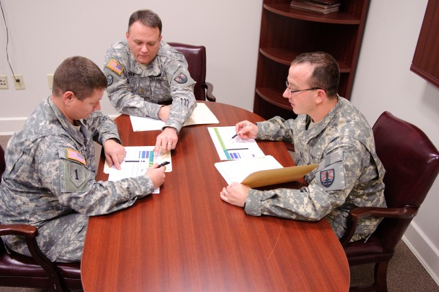 Three members of the 279th AFSB's Contingency Contracting Team, from left, Sgt. 1st Class Johnny Stewart, Maj. Allen Cheek and Capt. Chad Picket review schedules for an upcoming project. The trio is at Anniston Army Depot for training.