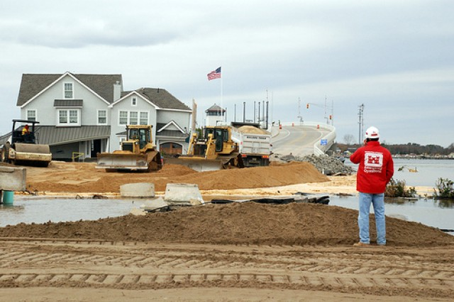 An Army Corps of Engineers employee inspects an ocean breach at Mantoloking, N.J., as a result of Hurricane Sandy.