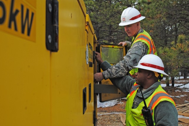 Sgts. William Davenport and Wayne Myers, of Delta Company, 249th Engineers, Fort Belvoir, Va., troubleshoot a generator at Lakehurst, N.J.