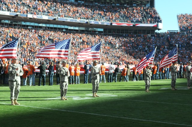 "DENVER "" Soldiers of 2nd Brigade Combat Team, 4th Infantry Division, hold flags during the Denver Bronco's ""Military Salute to Service"" at Sports Authority Field at Mile High in Denver, Nov. 18, 2012. Soldiers led Bronco players onto the field during the pregame ceremony, which included a singing of the national anthem and a fly over by the Air force."