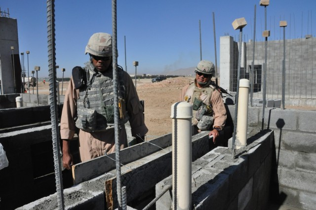 Ira Dorsett, a structural engineer, (left) and Benny Apuya, (right) a quality assurance and construction representative, both with the Afghanistan Engineer District - South inspect the masonry block work for a concrete sink at the Kandahar Regional Military Training Center construction site Nov. 18.