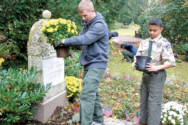 Troop 65 Boy Scouts Nathaniel Curtis and Jarred Edwards plant flowers at the foot of the monument at the American Children's Cemetery in Frankfurt.
