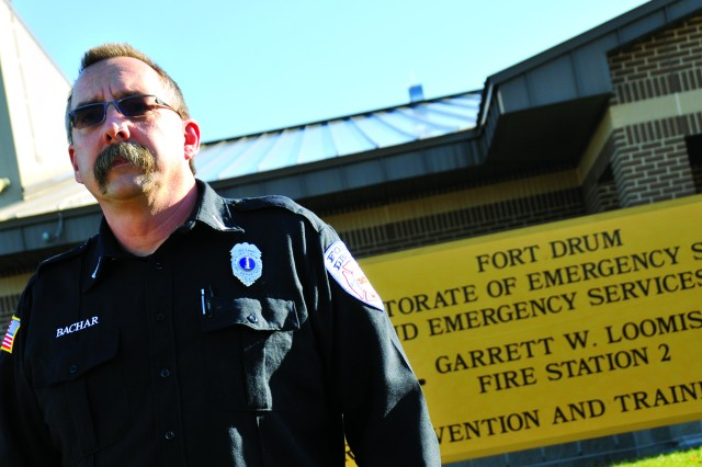 Lt. Kip Bachar, Aircraft Rescue and Firefighting Company lead firefighter at Fort Drum's Fire Station 3, stands in front of Fort Drum's Garrett W. Loomis Fire Station 2 on Ontario Drive, which was dedicated in Loomis' honor in July 2011.
