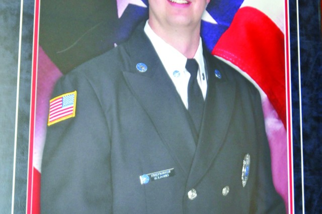 A photo of Garrett W. Loomis, a Fort Drum firefighter and volunteer with Sackets Harbor Volunteer Fire Department who lost his life in the line of duty, hangs at the entrance of Garrett W. Loomis Fire Station 2, where a display containing Loomis' firefighting gear is encased alongside it as a memorial to the young firefighter.