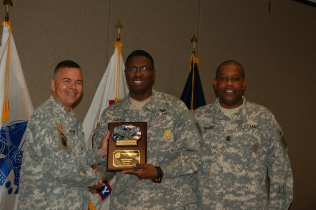COL Michael Faruqui, commander, Second Recruiting Brigade and CSM Milton Rhodie, Second Recruiting Brigade Sergeant Major, flank 1SG Jonathan D. Jackson, as he receives Second Brigade's Award for First Sergeant of the Year, 2012.