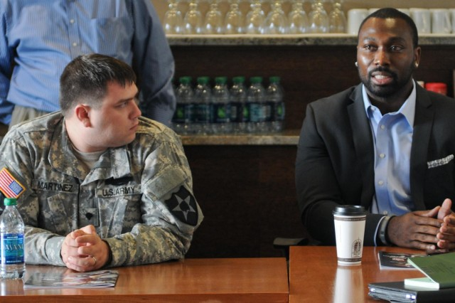 Spc. Bryan Martinez, a Atascadero, Calif., native, now a squad automatic gunner with 2nd Stryker Brigade Combat Team, 2nd Infantry Division, listens as Kerry Carter, a former NFL player, speaks about traumatic brain injuries. Martinez and Carter were part of a group of Soldiers and former players who participated in a discussion about TBI at Virginia Mason Athletic Center in Seattle, Nov. 20, 2012.