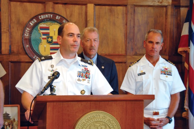 Col. Daniel Whitney (front), commander, USAG-HI, comments on the signing of a MOU as City and County of Honolulu Mayor Peter Carlisle (center) and Capt. Jeffrey James (left), commander, JBPHH, listen in during a ceremony at Honolulu Hale, Nov. 15.