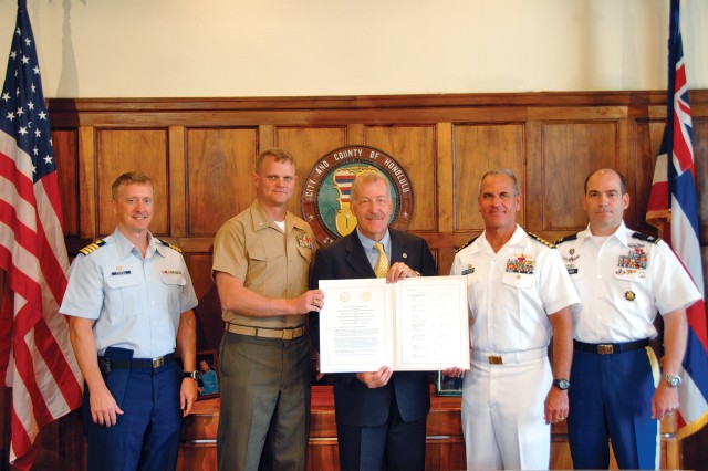 City and County of Honolulu Mayor Peter Carlisle (center) displays a signed copy of the MOU. Capt. Jeffrey James (second from right), commander, JBPHH, and Col. Daniel Whitney (right), commander, USAG-HI, along with Capt. James Koermer (left), commander, Coast Guard Base Honolulu, and Lt. Col. William Baker (second from left), command representative from Marine Corps Base Hawaii, participated in the signing ceremony as well.